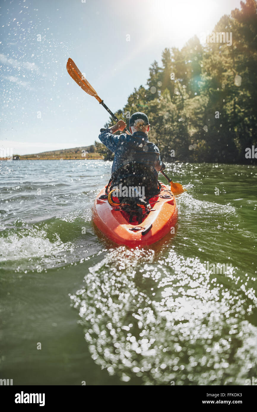 Rear view image of a mature man canoeing in a lake on a sunny day. Senior man paddling a kayak. - Stock Image