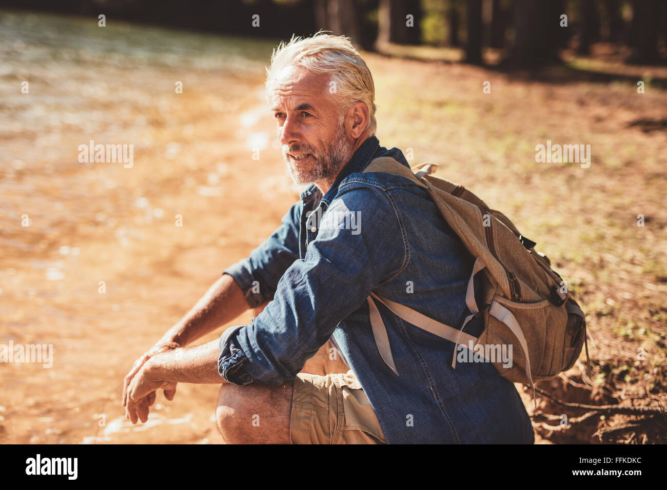 Portrait of senior male hiker sitting next to a lake and looking away. Mature man taking a break from his hike and - Stock Image