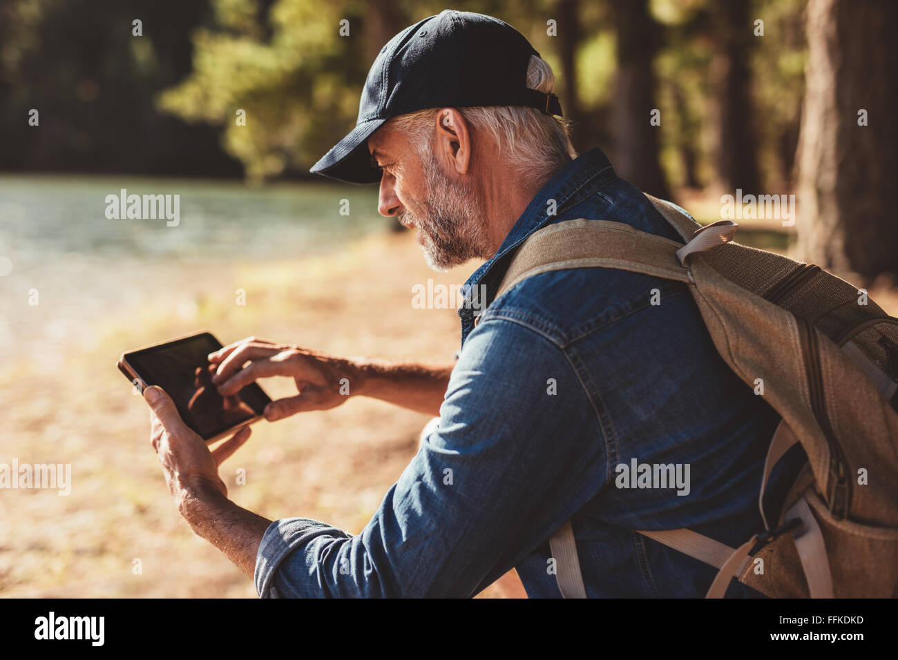 Portrait of mature male hiker using digital tablet outdoors. Senior man with backpack sitting by a lake looking - Stock Image