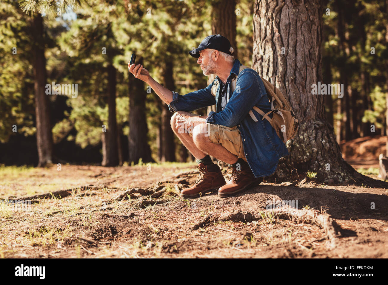 Mature man stops to check his position by using a compass while out on hike in the forest. male hiker sitting by - Stock Image