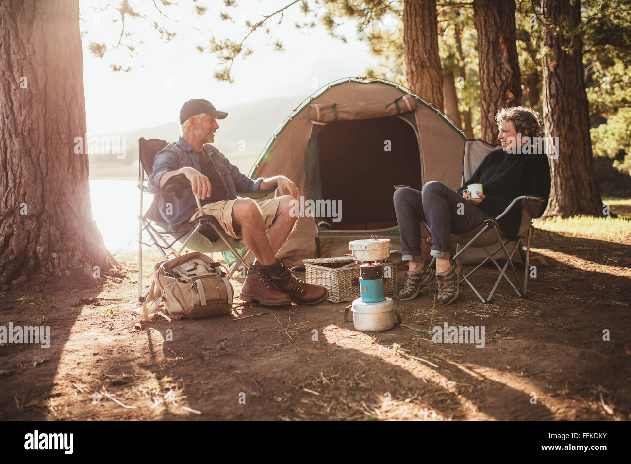 Portrait of happy senior couple sitting in chairs by tent at campsite. Mature man and woman relaxing and talking - Stock Image
