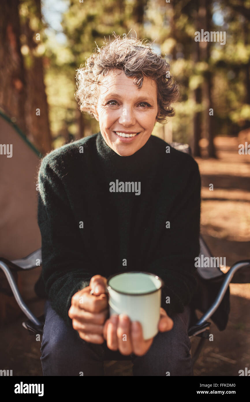 Portrait of senior woman sitting outside the tent with a cup of coffee. Caucasian female holding a coffee cup looking - Stock Image