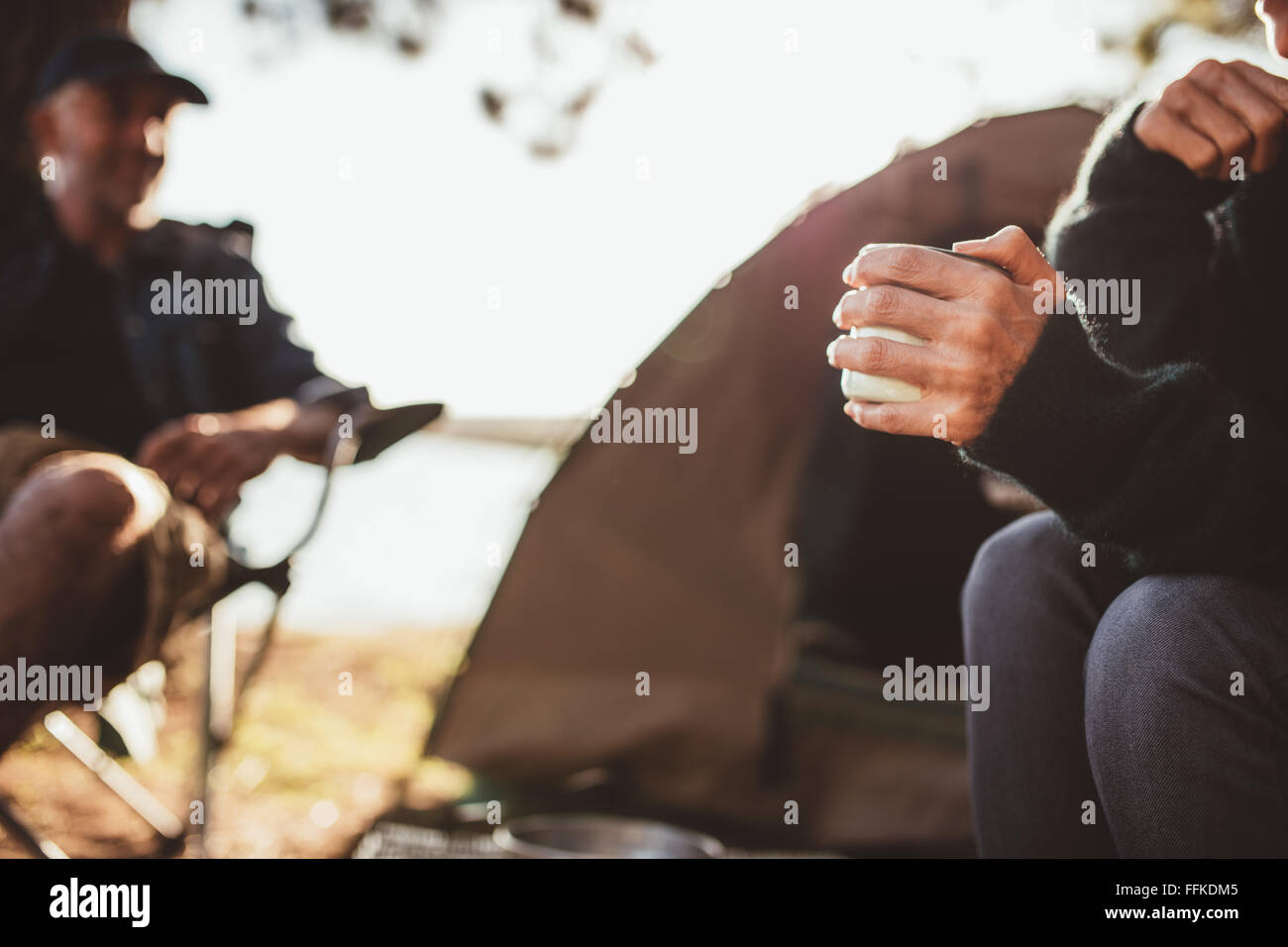 Close up portrait of a hand of a woman holding coffee at campsite with a man in background, both sitting outside Stock Photo
