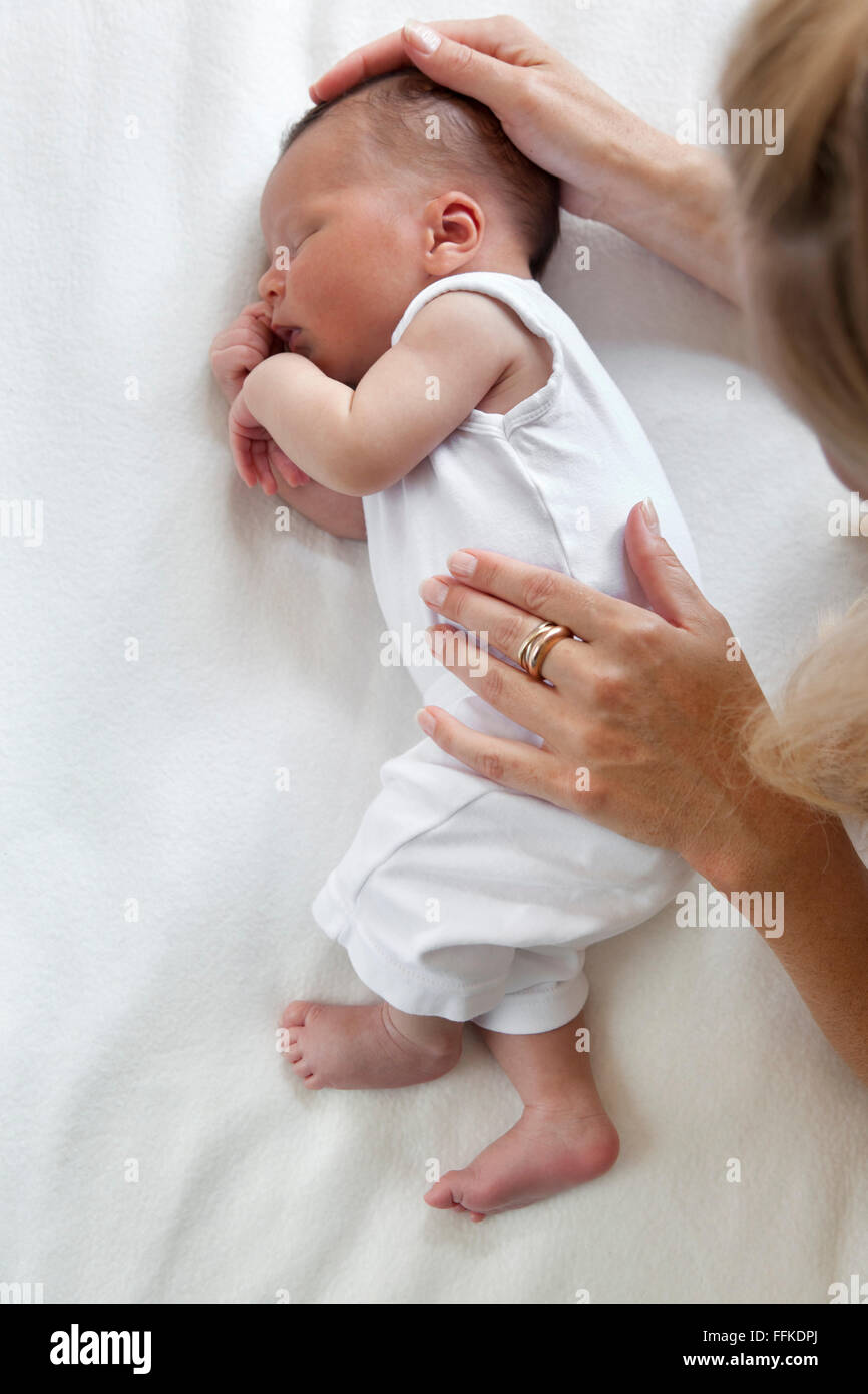 Sleeping newborn baby full lenght with mothers hands - Stock Image