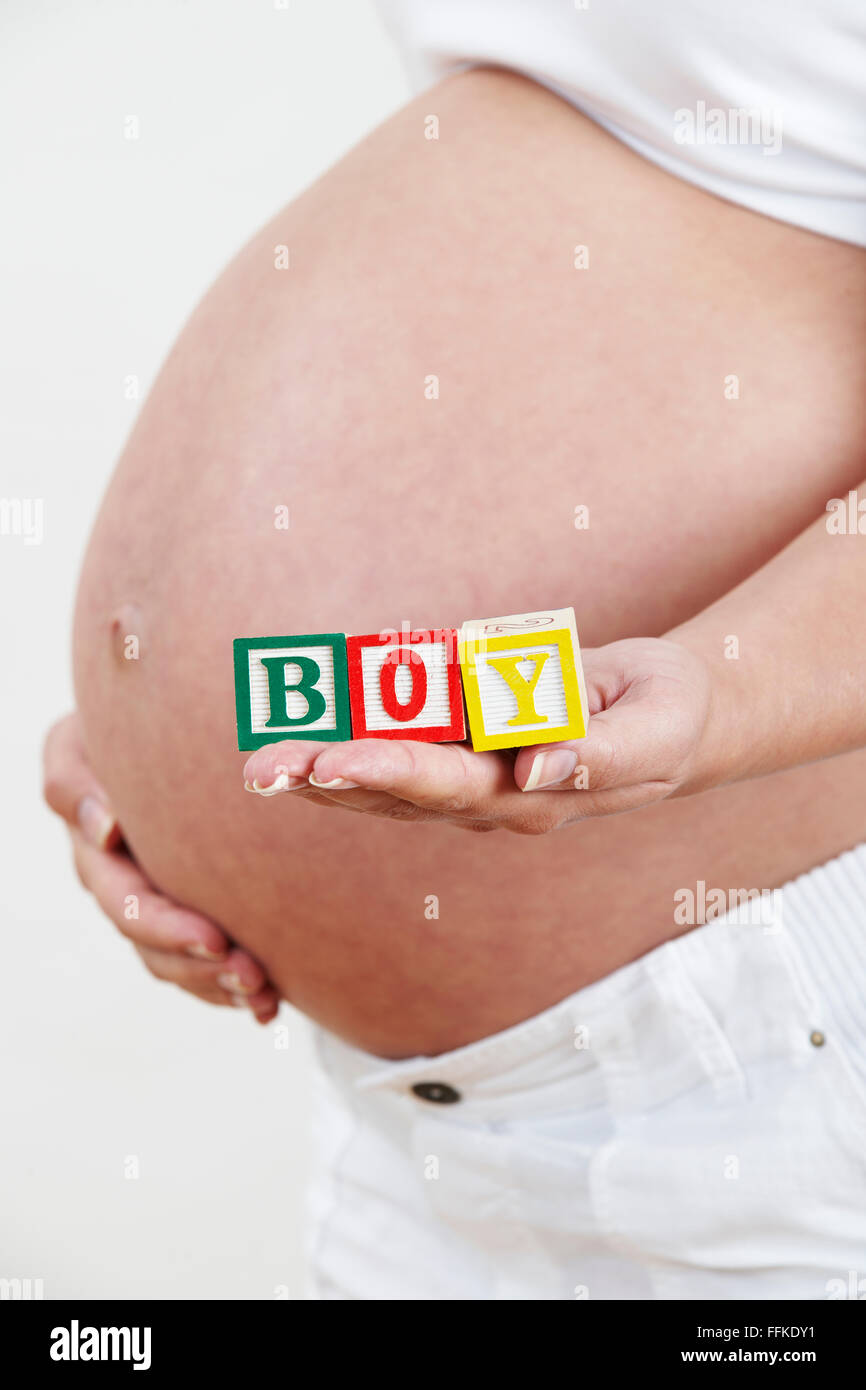 Close Up Of Pregnant Woman Holding Blocks Spelling BOY - Stock Image