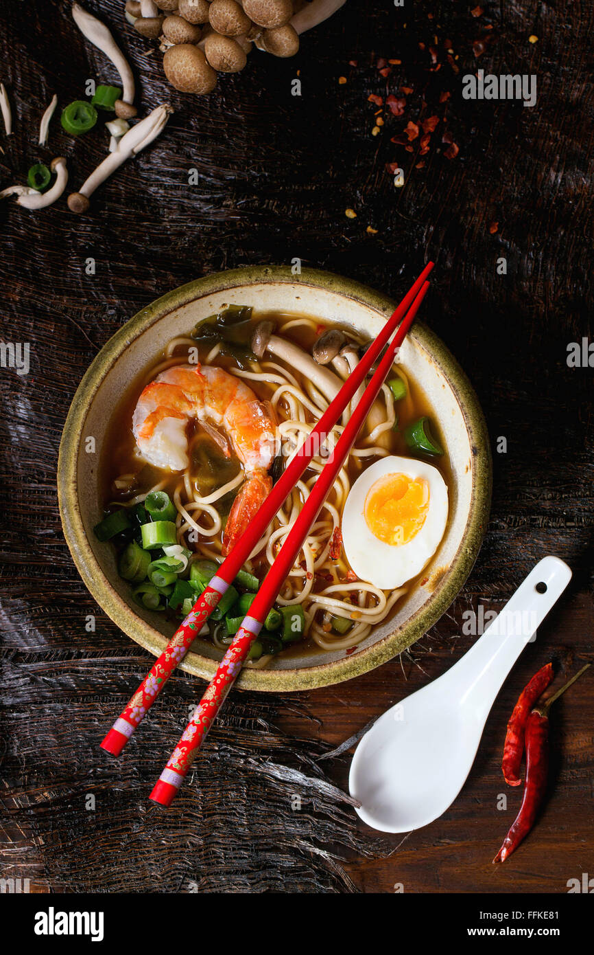 Ceramic bowl of asian ramen soup with shrimp, noodles, spring onion, sliced egg and mushrooms, served with red chopsticks Stock Photo