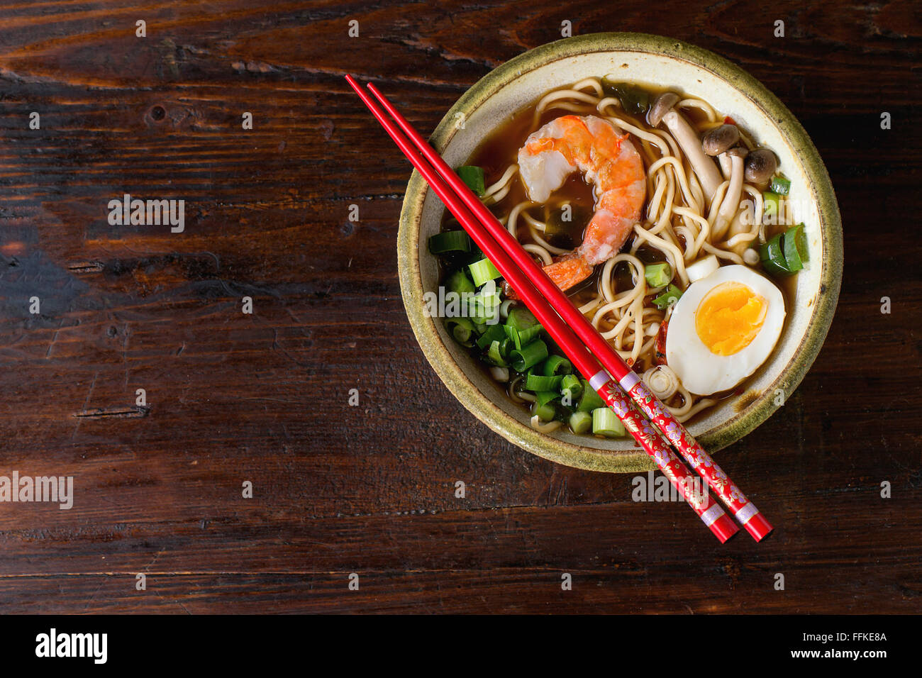 Ceramic bowl of asian ramen soup with shrimp, noodles, spring onion, sliced egg and mushrooms, served with red chopsticks - Stock Image