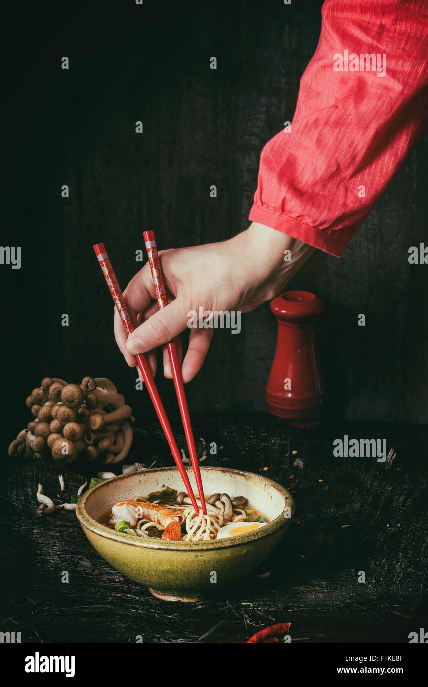 Female hand in red shirt take by red chopsticks noodles from asian ramen soup with shrimp, onion, sliced egg and - Stock Image
