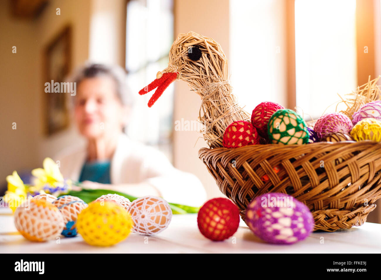 Basket with Easter eggs and hen in senior woman house Stock Photo
