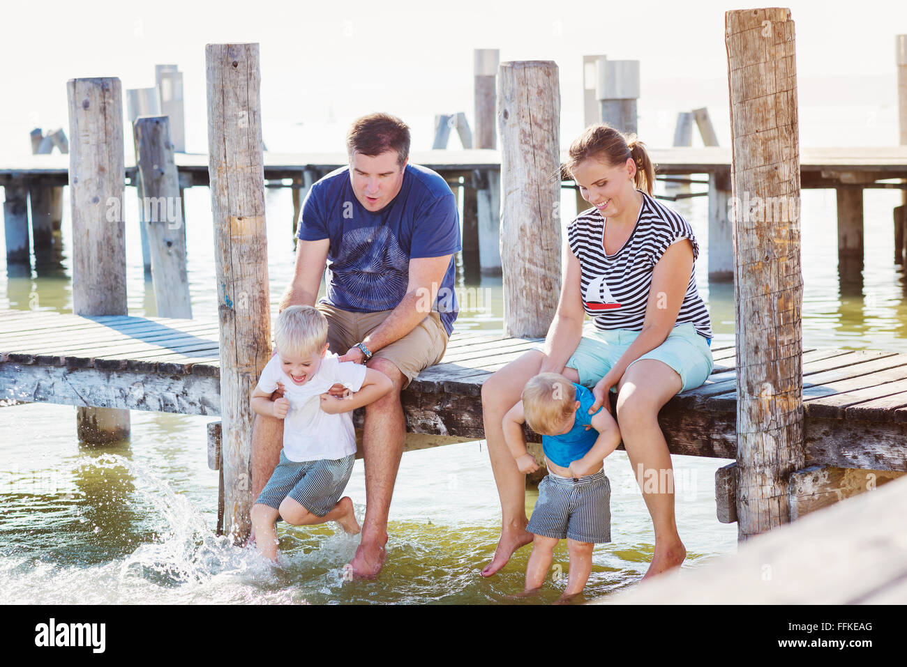 Family sitting on the pier, above water, sunny summer - Stock Image