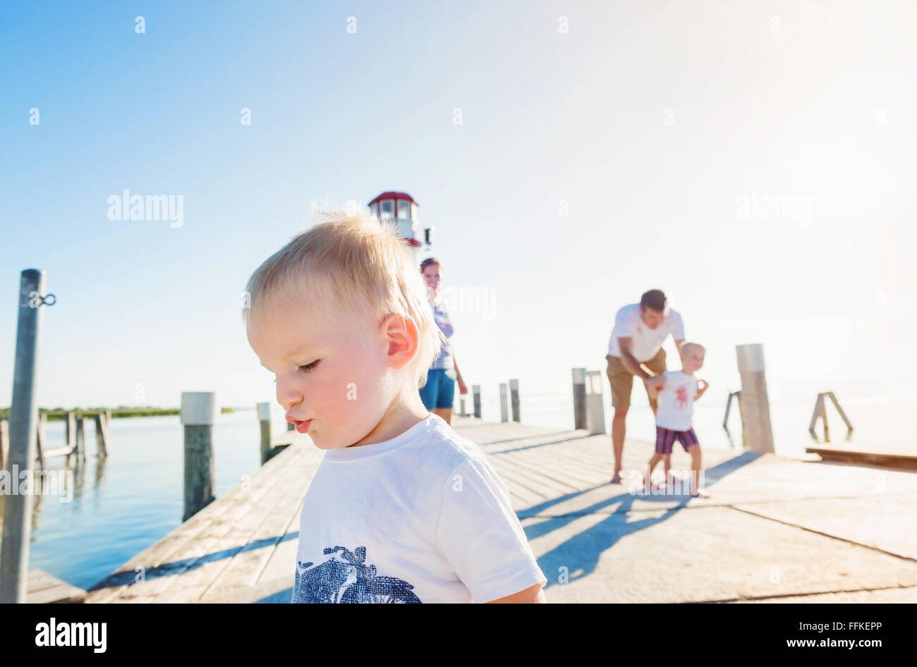 Family on the pier at the lighthouse, sunny summer - Stock Image