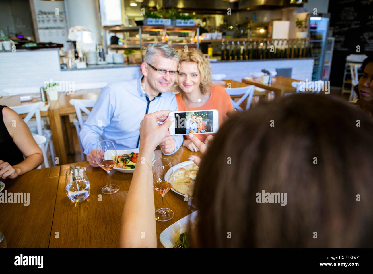 Taking a picture of friends in restaurant - Stock Image