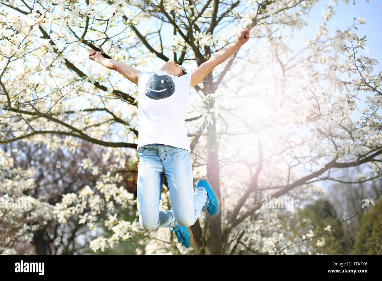 It's summer, it is fun :). Summer sunny day, relaxing in the countryside. A child jumps high in the spring morning - Stock Image