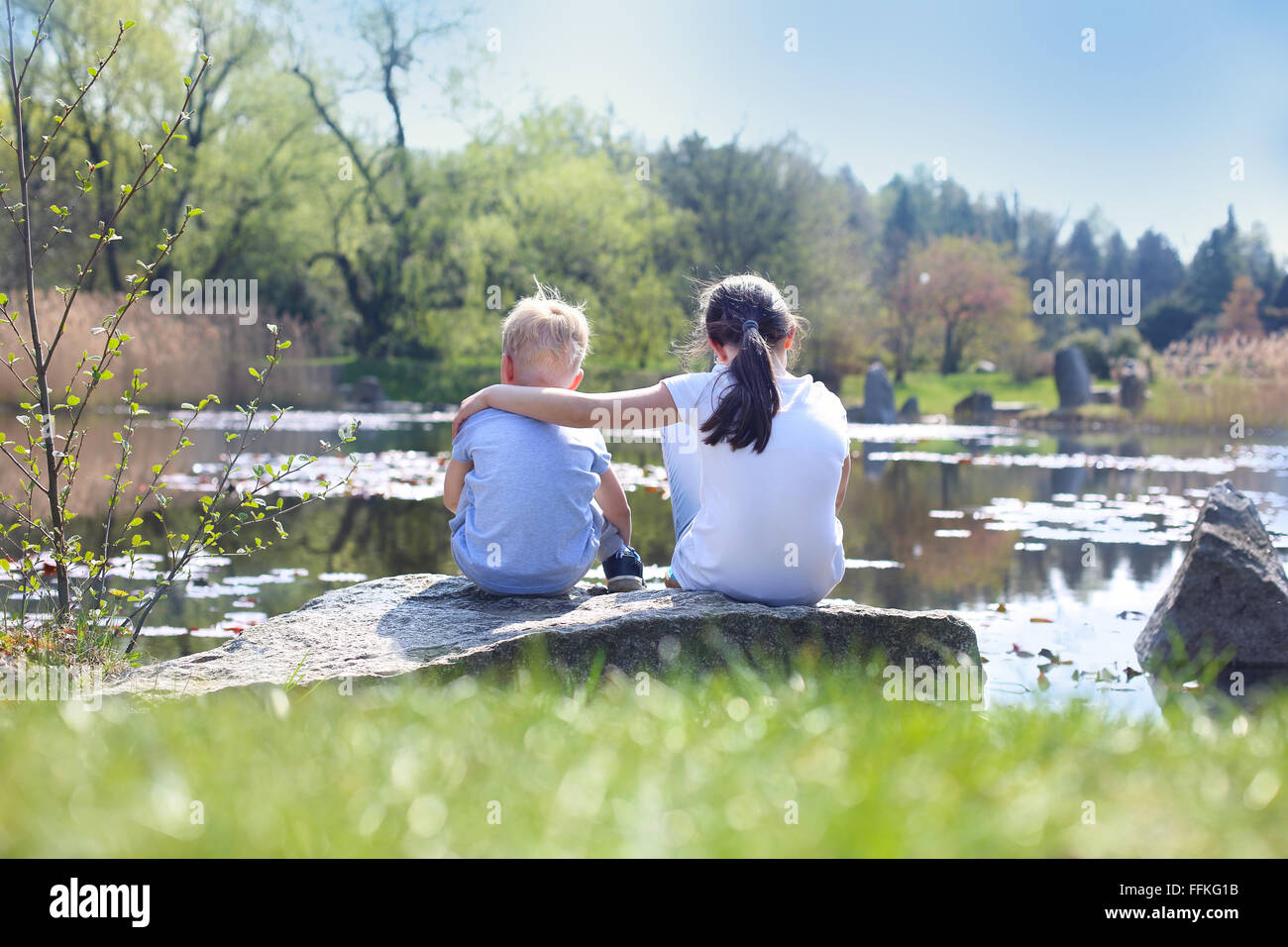 Holiday time relaxing by the water. Two children, older sister and younger brother sitting on the shore of the lake - Stock Image