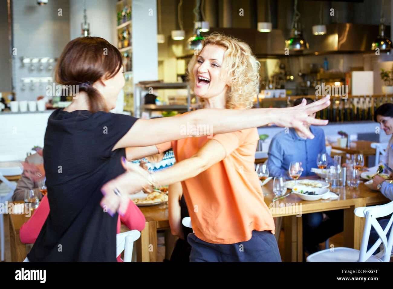 Girlfriends in restaurant rejoice to meet again - Stock Image