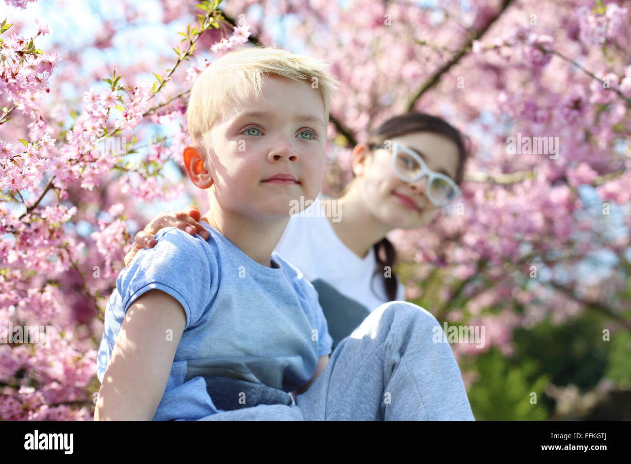 Siblings. Happy child. Boy sitting under a tree, the girl in the backgroun - Stock Image