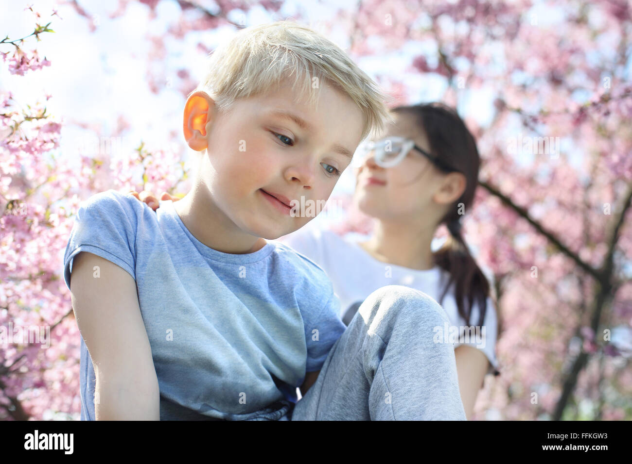 Siblings. Happy child. Boy sitting under a tree, the girl in the background - Stock Image