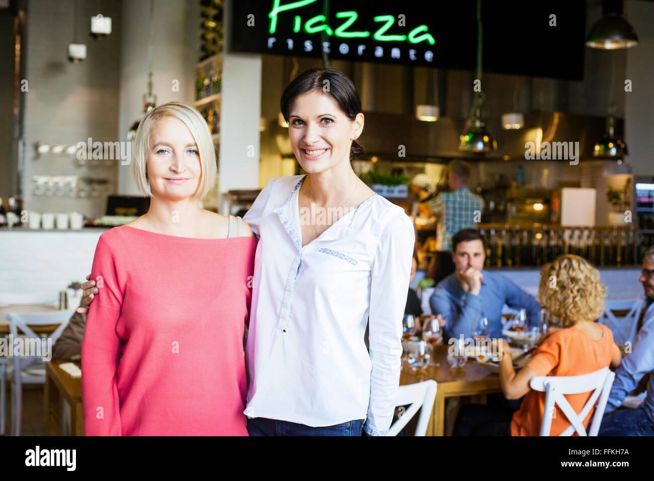 Portrait of girlfriends in restaurant - Stock Image