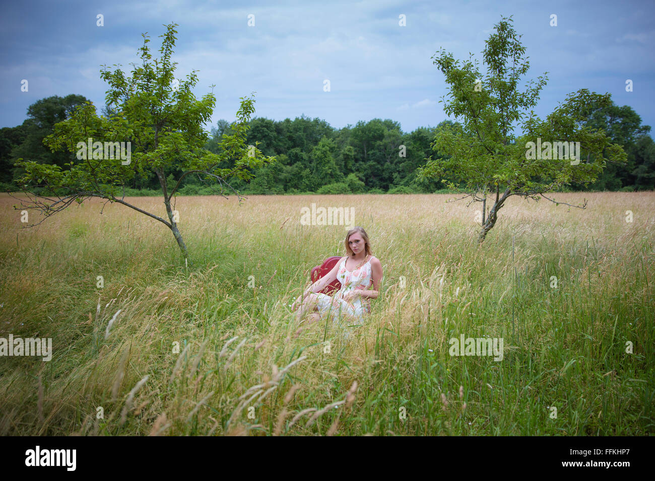 Beautiful Blond Woman Sitting In A Red Chair Out In A Field