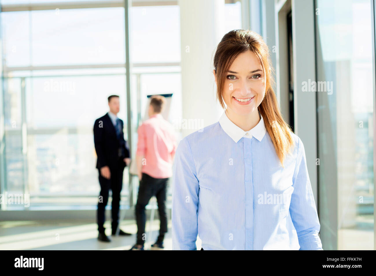 Well-dressed businesswoman with colleagues in background - Stock Image