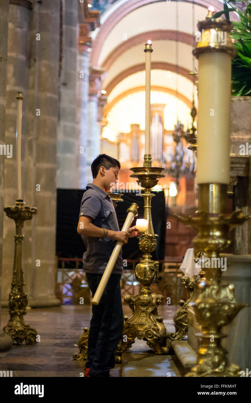 Oaxaca, Mexico - An altar server lights candles at the Cathedral of Oaxaca. - Stock Image