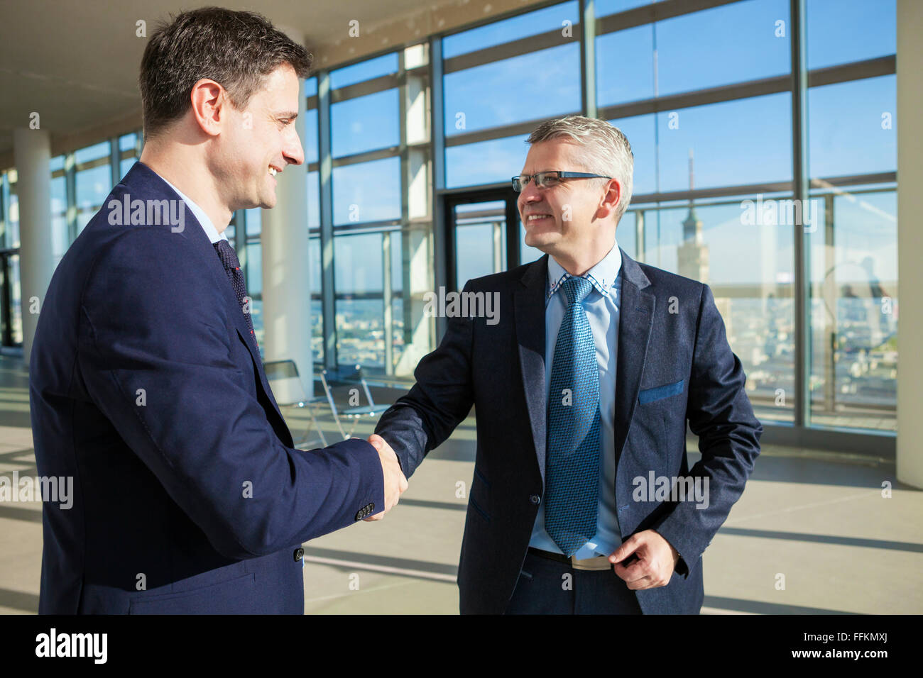 Two businessmen shaking hands in modern office - Stock Image