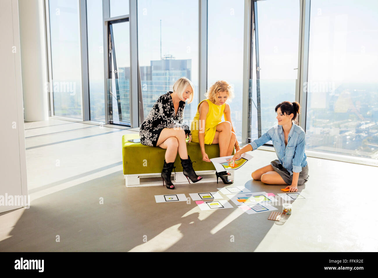 Three female architects in business meeting against urban skyline - Stock Image