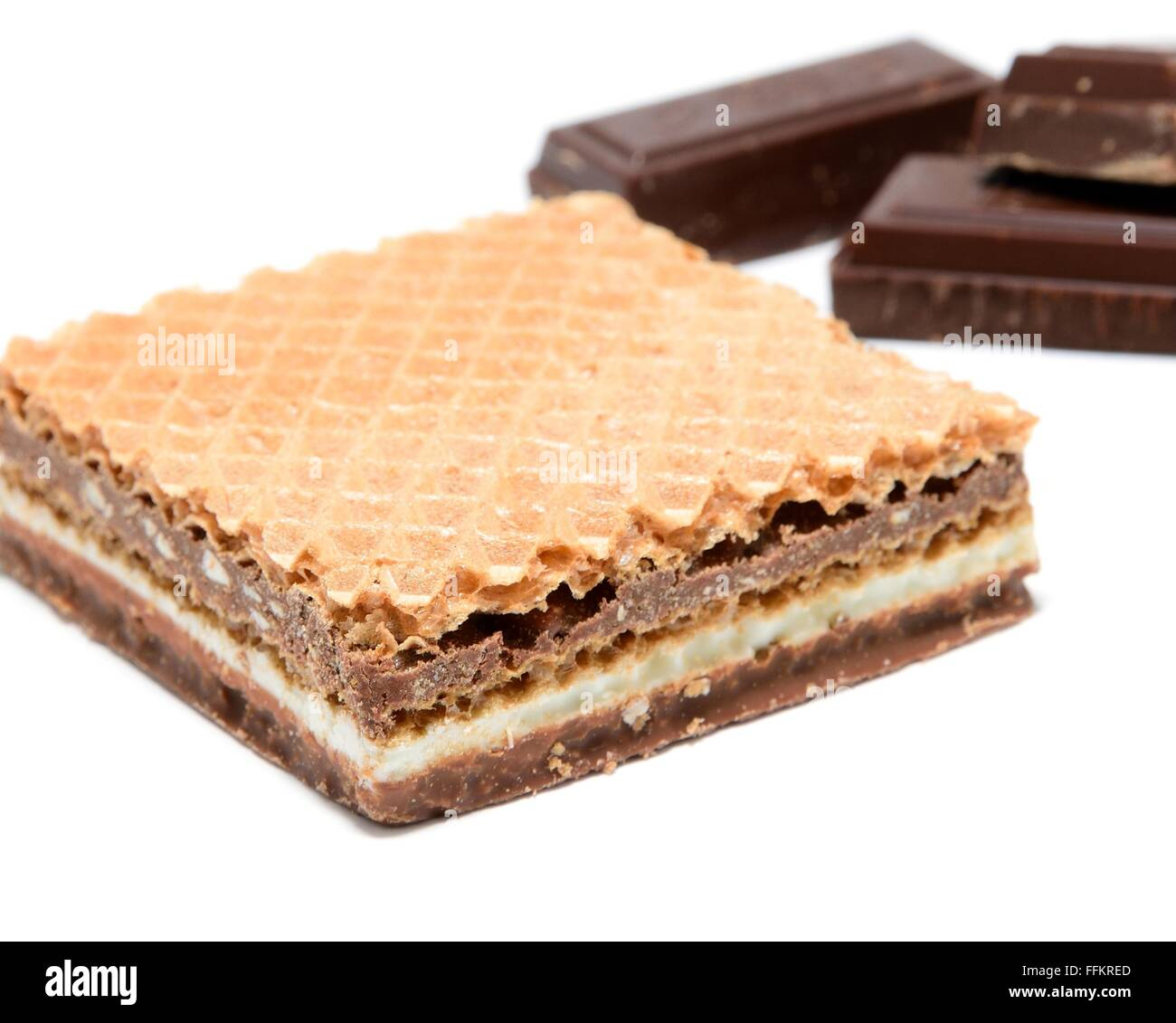 Wafer with hazelnut and milk cream with pieces of dark chocolate on white background. - Stock Image