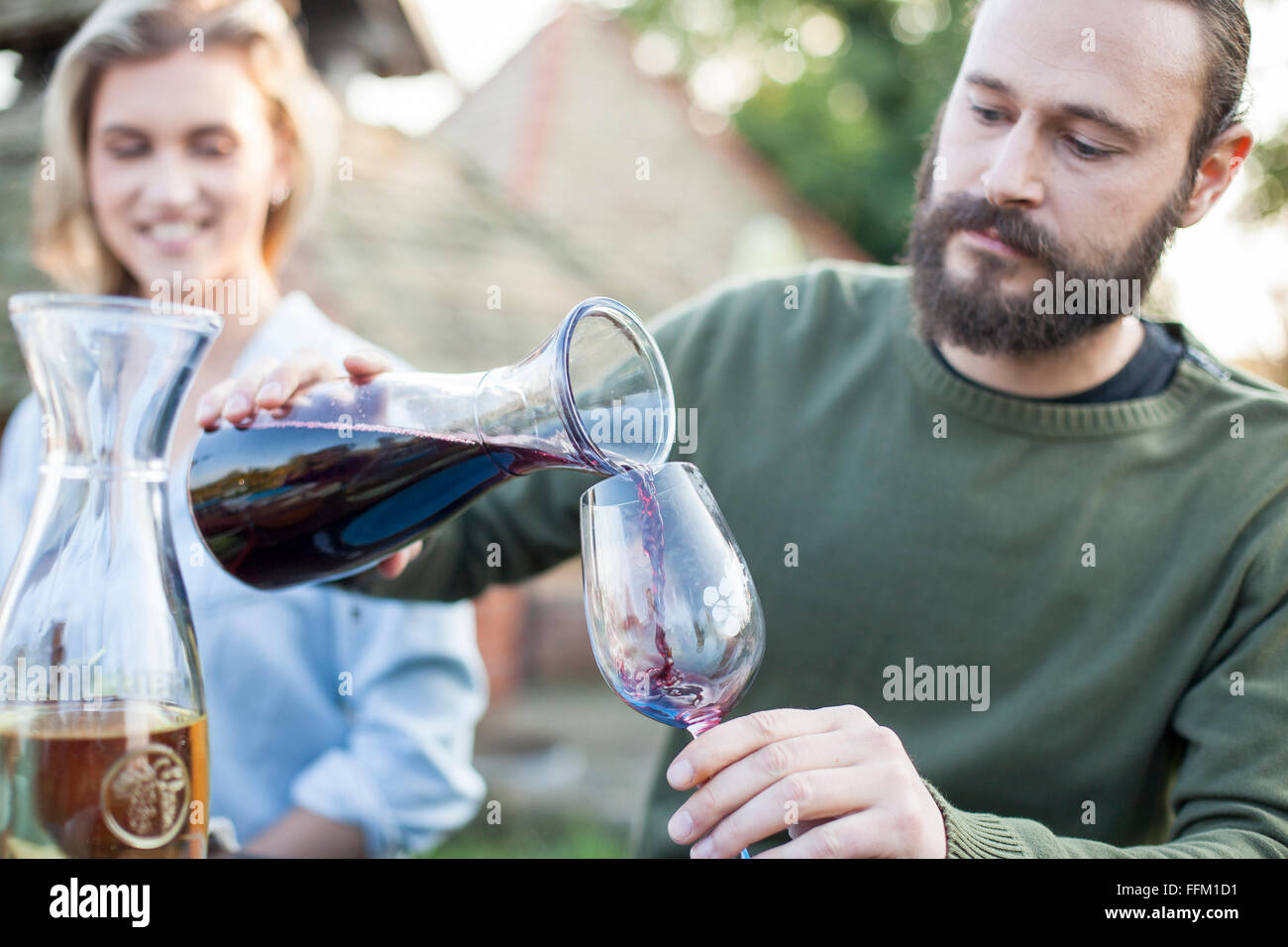 Man pouring red wine on garden party - Stock Image