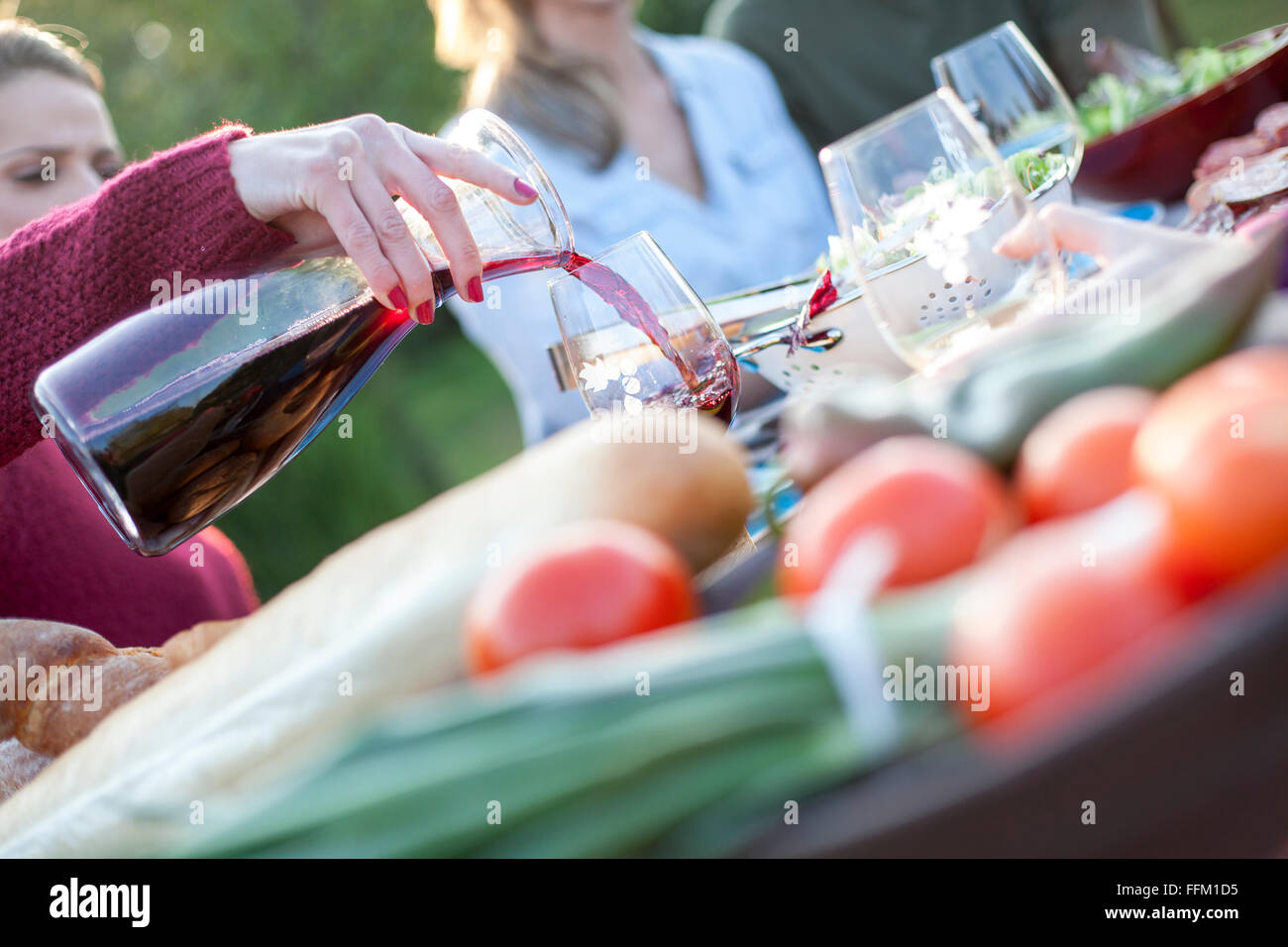 Pouring red wine into glass on garden party - Stock Image