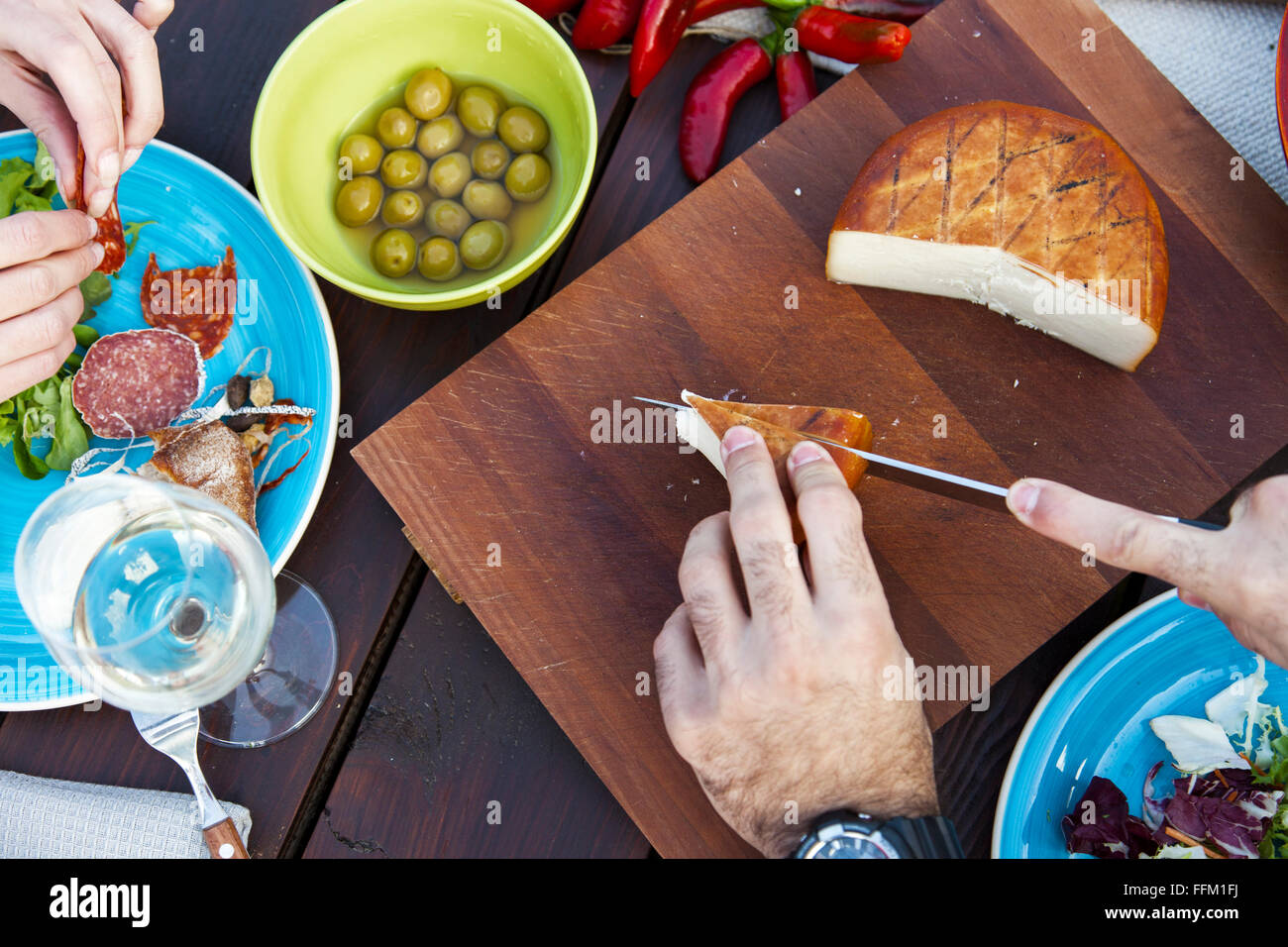 Man cutting cheese on garden party - Stock Image
