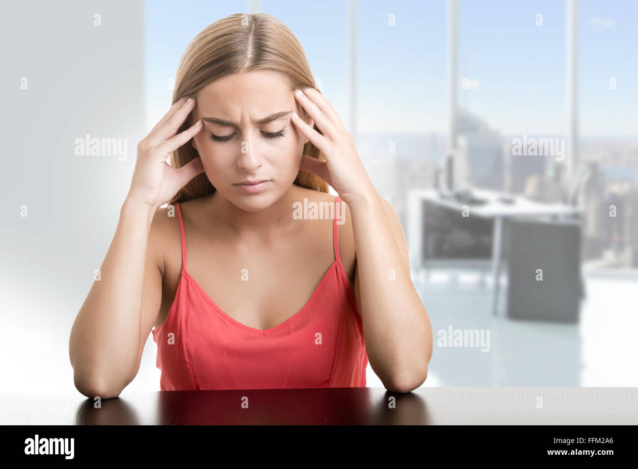 Woman suffering from an headache, holding her hand to the head, in an office - Stock Image