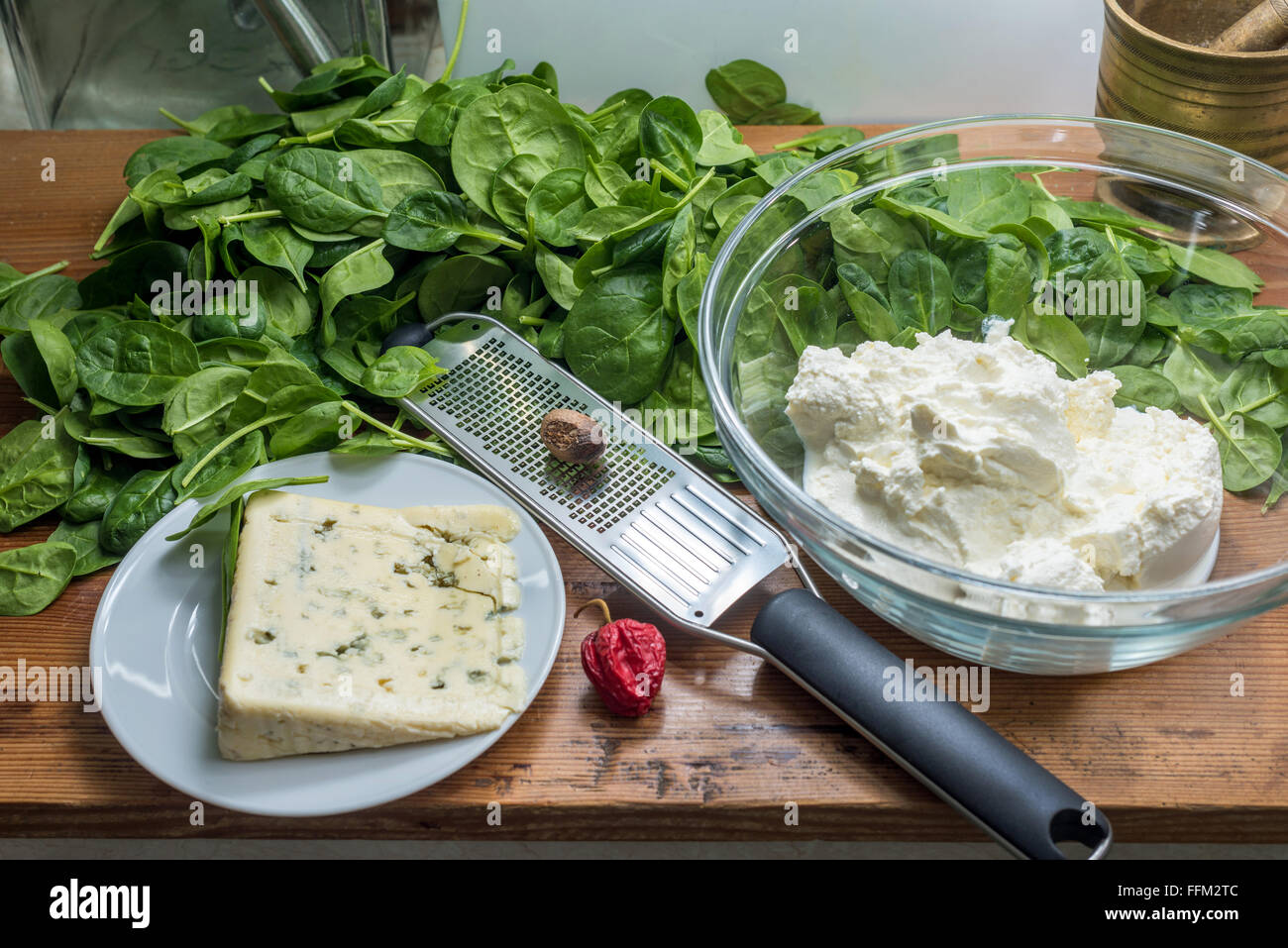 made ravioli pasta by hand Hand Kitchen Spinach Ricotta Cotta dough stamp Ravioli stamp cut out cheese cream cheese - Stock Image