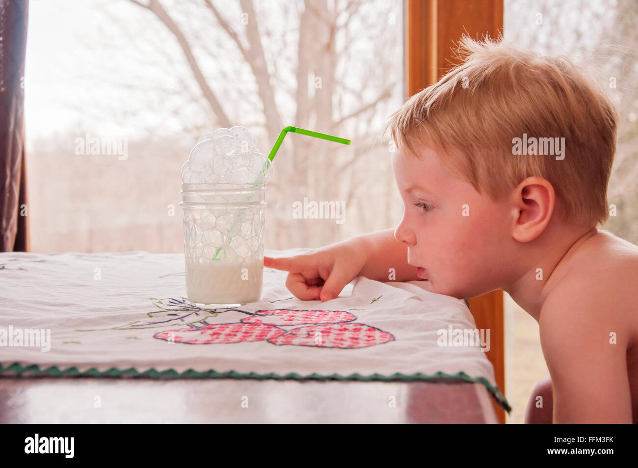 Child pointing at glass half full - Stock Image