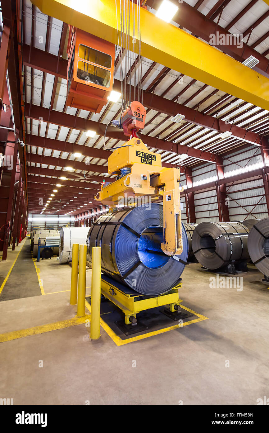 Claw grabber placing coil onto coil cart - Stock Image