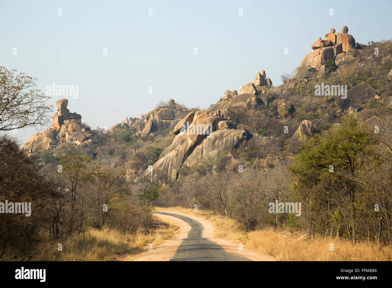 Scenic view of the access road to the Matobo National Park showing large granite boulder koppies - Stock Image