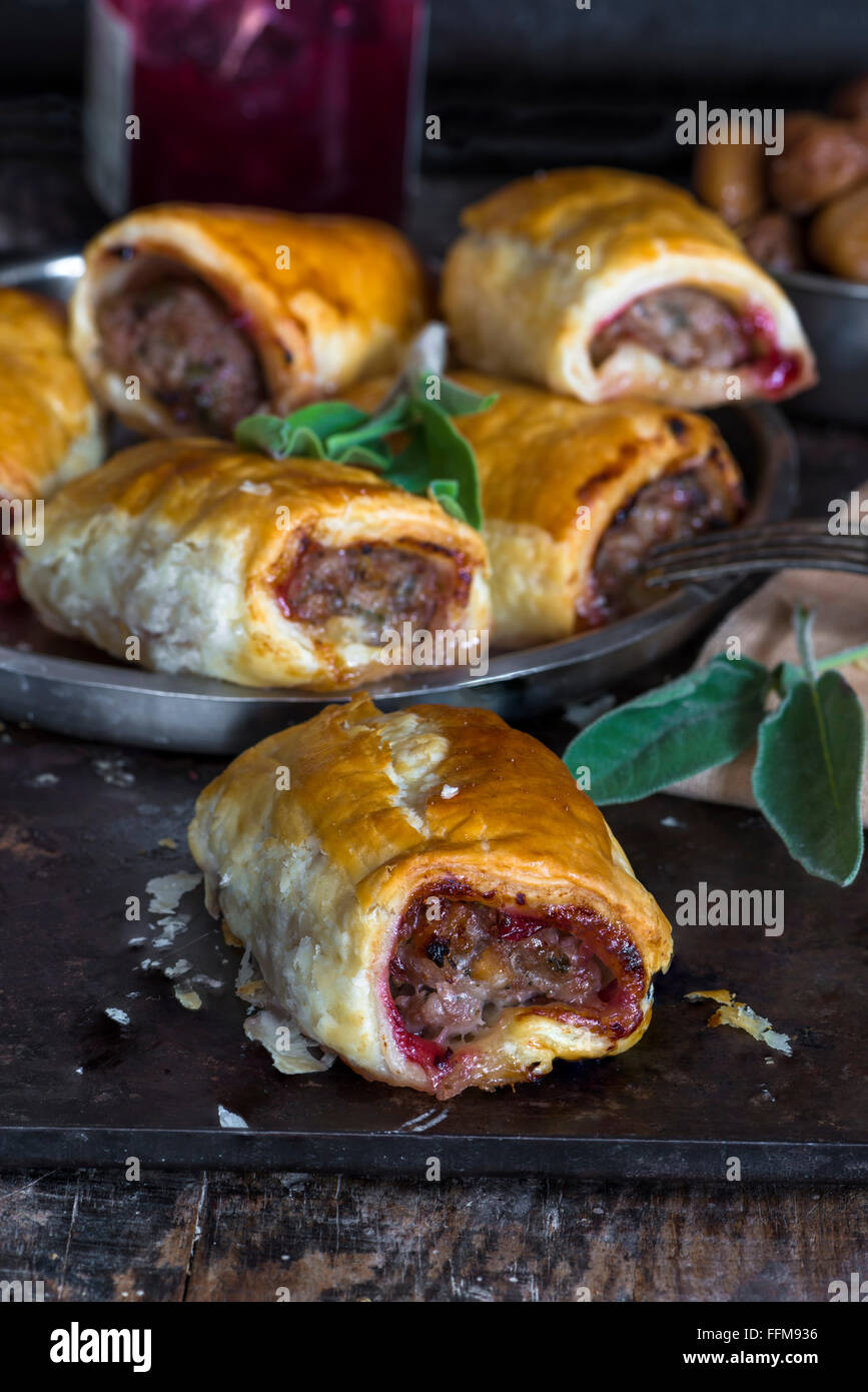 Homemade pork sausage rolls with chestnuts, cranberry sauce and sage - Stock Image