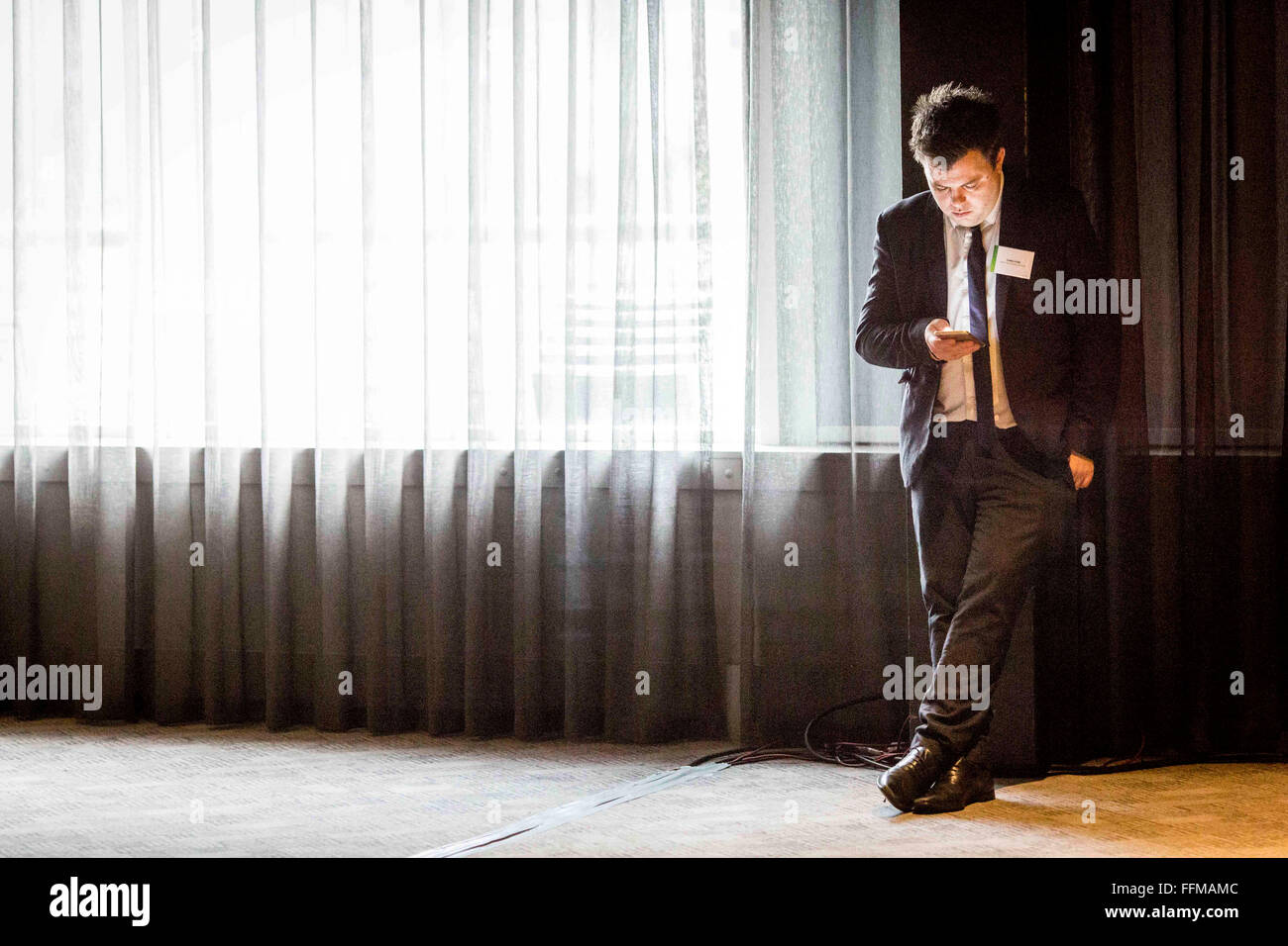 a man in a suit looks at his mobile phone - Stock Image