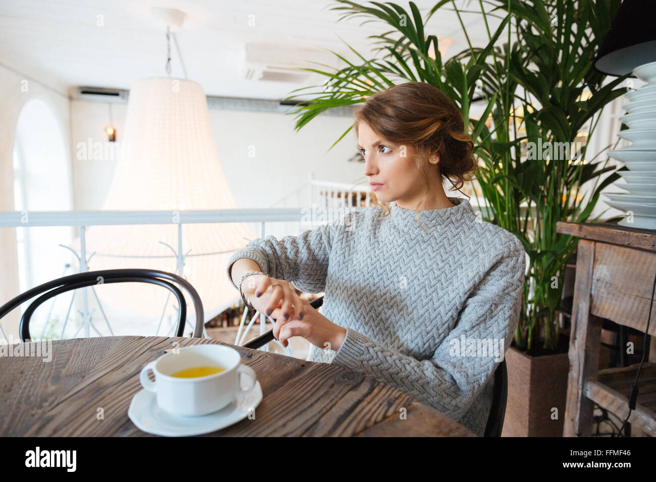 Woman waiting for somebody in cafe - Stock Image