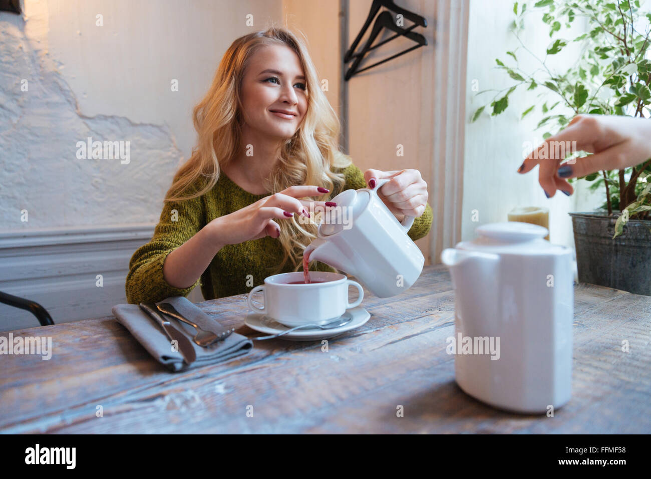 Beautiful young woman drinking tea in cafe - Stock Image