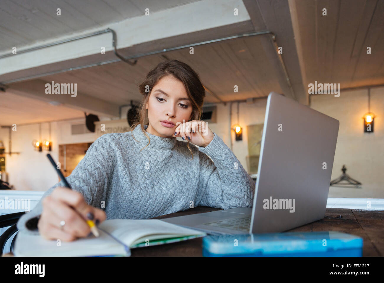 Woman working with laptop computer and notepad in cafe - Stock Image