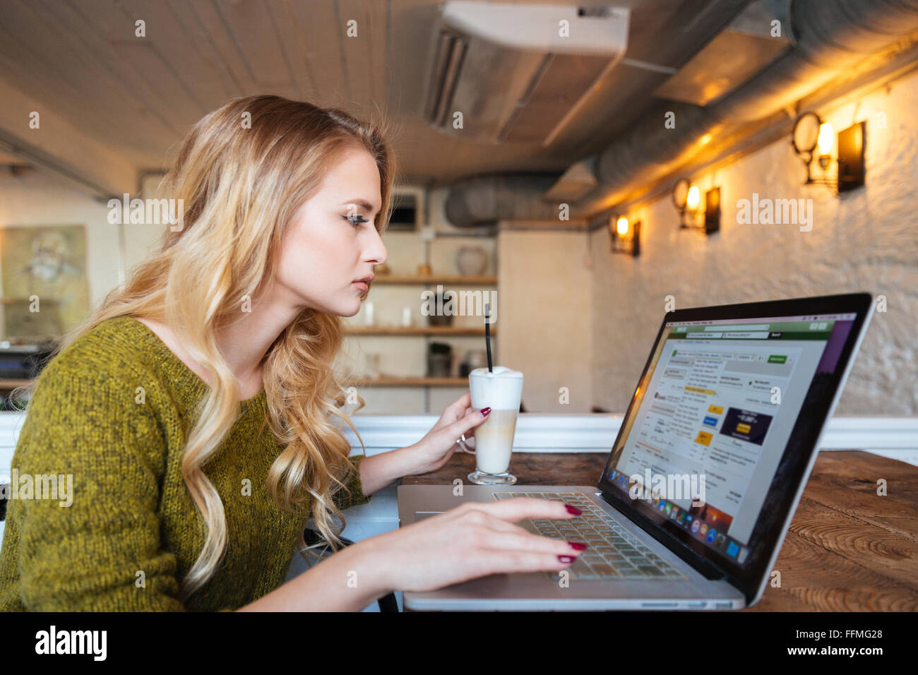 Blonde woman using laptop computer in cafe Stock Photo