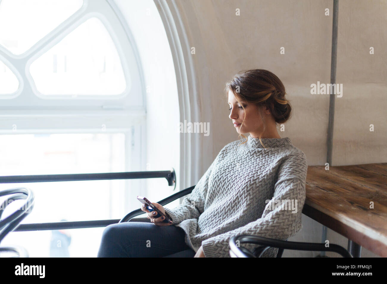 Young beautiful woman using smartphone in cafe - Stock Image