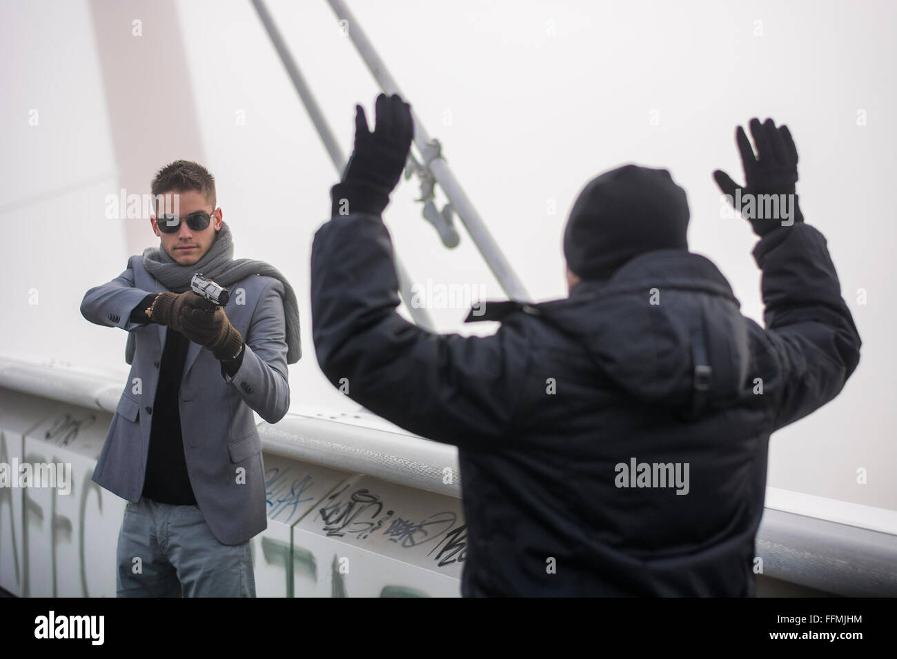 Killer drawing a bead on unrecognizable person while standing on foggy bridge - Stock Image