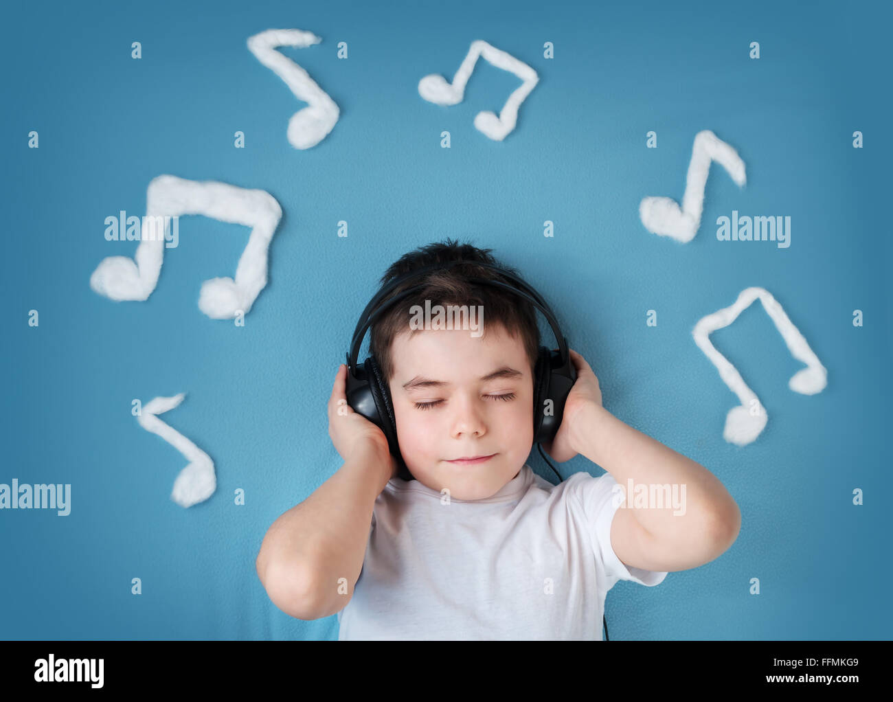 little boy on blue blanket background with headphones Stock Photo
