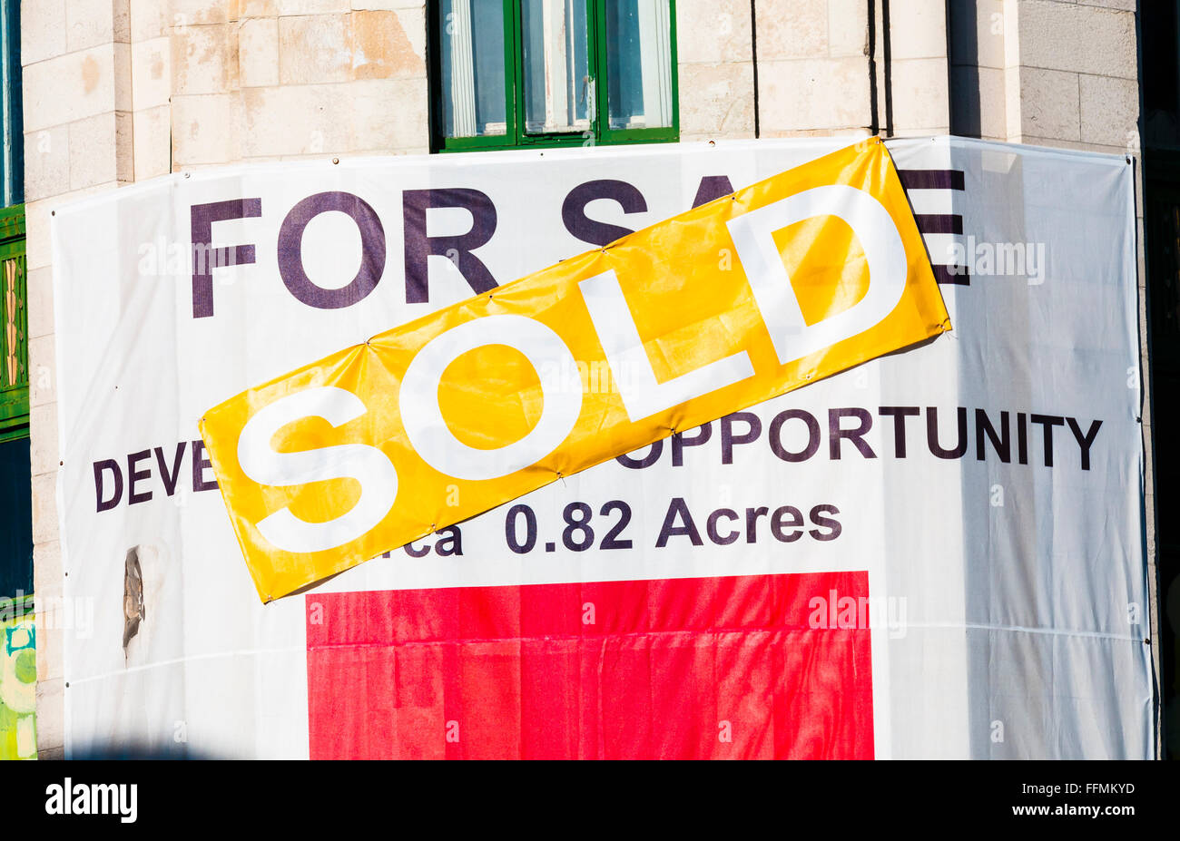 Estate agent sign on a commercial property advising that it has been sold. - Stock Image