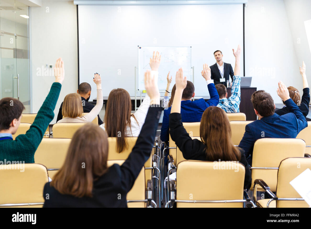 Speaker answering the questions of audience on business conference in  meeting hall - Stock Image