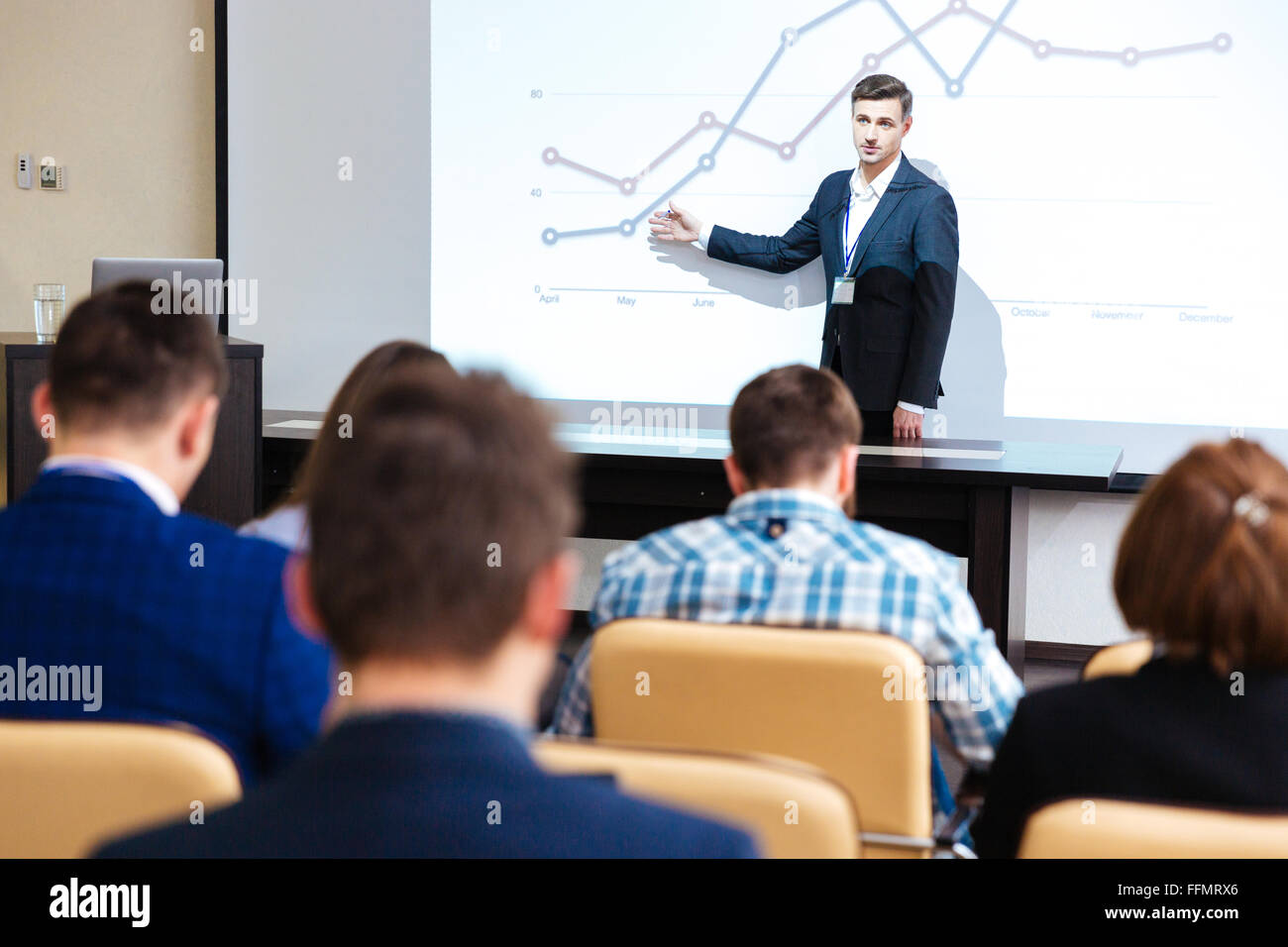 Inelligent speaker standing and lecturing at business conference in boardroom - Stock Image