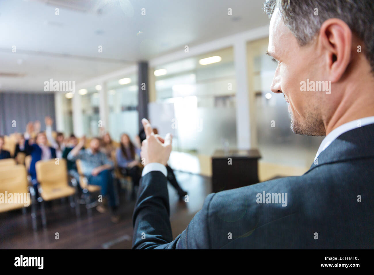Closeup of speaker pointing to audience on business conference in meeting hall - Stock Image