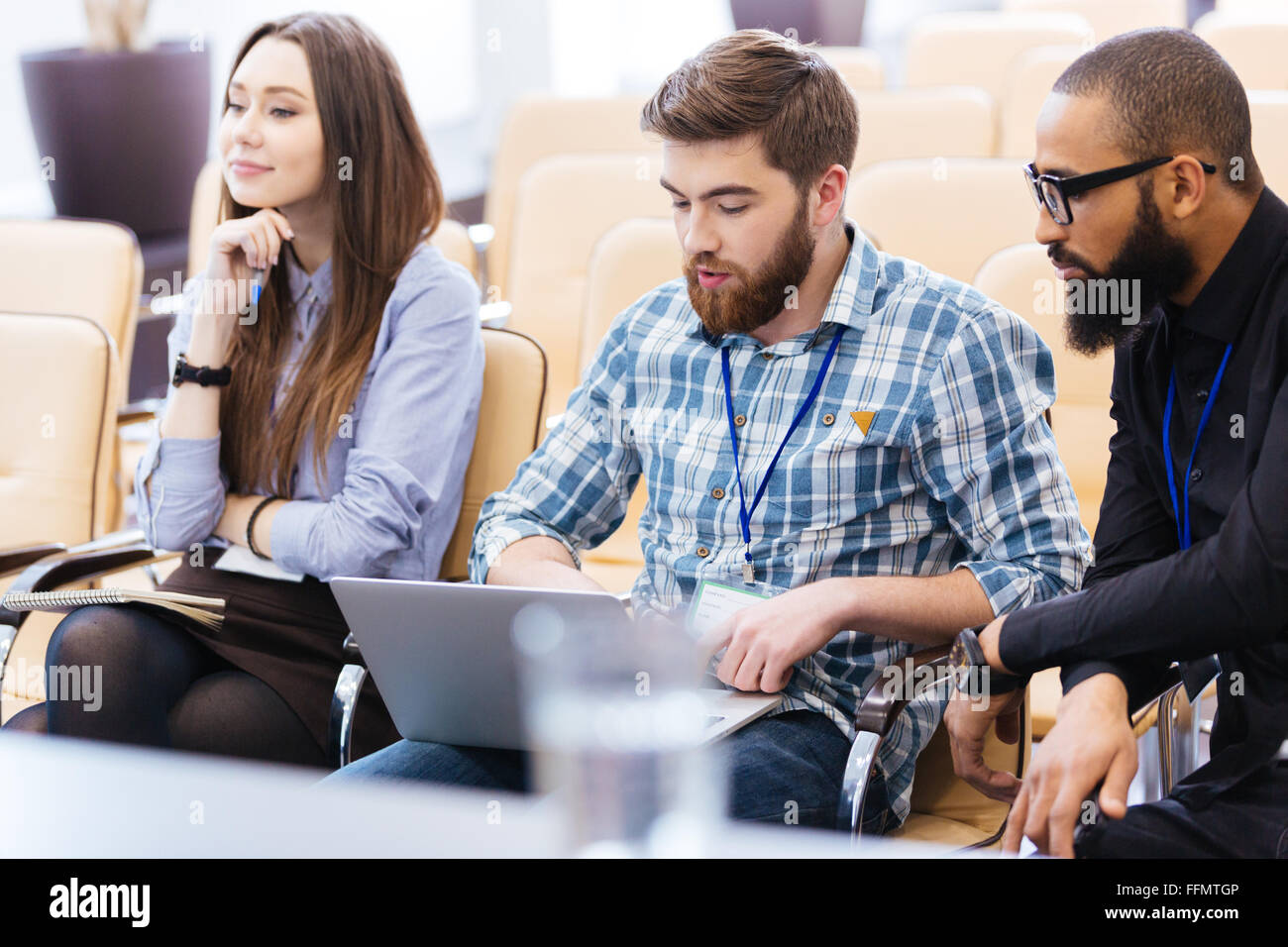 Multiethnic group of young business people using laptop sitting on meeting in conference hall - Stock Image